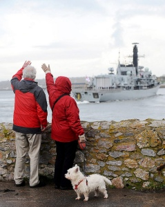 People waving to Royal Navy Ship