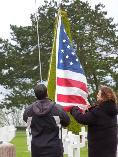 U.S. flag being raised above the graves at Normandy American Cemetery and Memorial